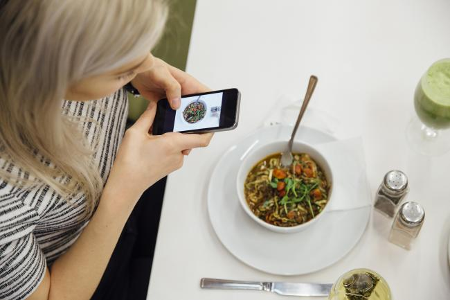 Young woman using her smartphone to take a photo of her vegan meal