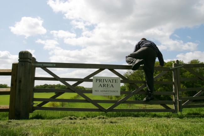 A man climbing over a gate into a 'Private area'