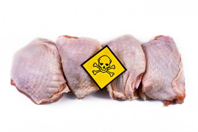Raw chicken meat with yellow poisonous skull warning sign