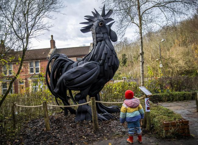Three year old Ana looks up at an art sculpture of a rooster created by artist Sabolc Vas out of recycled tyres. Picture: SWNS